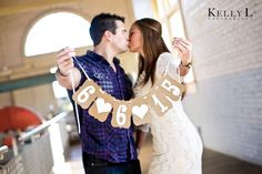 cute save the date engagement photo idea with wedding date hung on banner with hearts