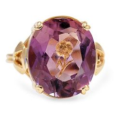 This Retro-era ring showcases a gorgeous amethyst, carved with a flower intaglio that is lined with a 24k gold flake. (Amythest approx. 6.00 total carat weight).