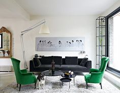 """A modern interpretation of """"The Last Supper"""" hangs above a velvet charcoal sofa in the chic living room of the home of Cendrine Dominguez, featured in Marie Claire Maison. Black Sofa, Gray Sofa, Green Armchair, Green Chairs, White Chairs, Living Room Decor, Living Spaces, Living Rooms, Eames"""