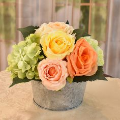Decorate your home with a splash of color. A beautifully hand crafted designer bouquet created with roses in peach, coral, and  yellow with green hydrangea for accent. Set in a  farmhouse metal planter. Great for a gift.  Perfect size for RVs & offices, accent tables, bedroom and baths. 9'' H x 8'' W x 8'' D