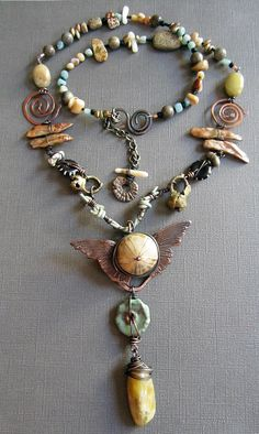 I challenged myself to make some longer necklaces this fall.  It's not my comfort zone, and I felt my work was getting too stale.  I wanted to make some longer pieces, yet still capture my eclectic style.  The travler was born, as I tried to use many beads, from many places and times.  The focal is a fossilized sea urchin, the wings are copper clay- for travel, the beads below the focal is marsha neal, some kind of opal drop, antique brass bells from india, handmade copper swirl connectors…