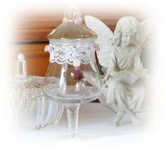 Diesen schönen antiken Glasbehälter mit Deckel habe ich mit einer Spitzenborde, Basteldraht und zarten Perlen in rose, weiß, klar, einer silbernen Schneckenperle, einem Strassrondell und facettiertem Herz bearbeitet. Das Glas kann als Bonboniere für Pralinès oder anderer Köstlichkeiten dienen.