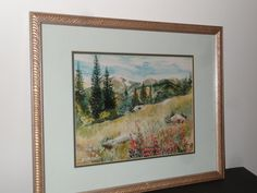 Lovely, framed watercolor painting wildflowers and Rocky Mountains by artist Alicia Bauer. Watercolor is 10.5 x 14. With frame, it is 17.5 x 21.5.