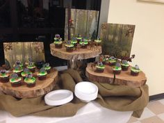The cupcake display stand was made from 3 thick slices of a tree, which were placed on risers. Burlap was tucked around to hide the risers.  Back drops are hunting themed scrapbook paper glued to styrofoam.  Zoom in to see the details including two hunters, tree stand, deer, moose etc.