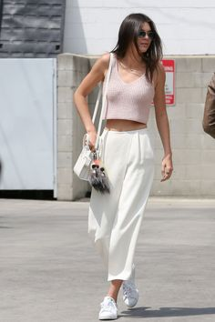 15 stylish sneaker outfit ideas to try this summer: Kendall Jenner wears her adidas sneakers with white culottes and a pink crop top