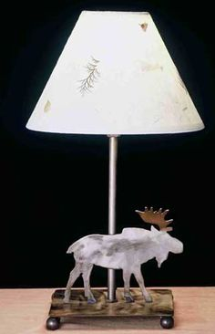 """A nature inspired moose accent lamp is topped with an ivory paper shade with pressed flowers. The table lamp is finished in antique copper and is handcrafted in the USA by artisans.Total: 14""""HShade: 5""""H x 8""""WBulb: CandleMax Watt: 25Custom Crafted In Yorkville, New York. Please Allow 28 Days. All duties, brokerage & border fees are included in this price!"""