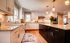 Dark and white wood cabinets are tied together with a neutral granite countertop and neutral walls. www.jamesriverconstruction.com