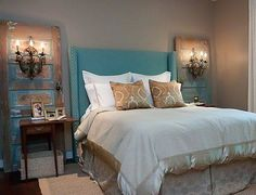 The unique pairing of reclaimed doors and vintage electric wall sconces create an elegant Shabby Chic bedroom. A skilled DIY homeowner could build this magnificent blue nail head trimmed headboard as a weekend project #designinterpreterblog #DesignerTip: Cheryl Hucks Interior Designs