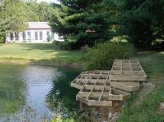 fixed dock patio at bank level with stairs off one end to the dock at water's edge and out over the water- photo of unfinished dock