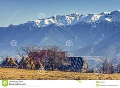 Peaceful rural mountain landscape with traditional Romanian mountainous farm with old wooden barn and haystacks in Moeciu, Brasov county, Trasylvania region, Romania.