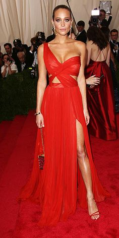 The Most Unbelievable Dresses at the 2015 Met Gala | HANNAH DAVIS | wearing a one-shouldered bright red J. Mendel dress with high slits, strappy bodice, and matching red sandals and a Kotur gold clutch.