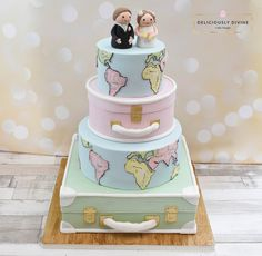 A travel cake or honeymoon cake with wedding peg couple on top. Peg bride and peg groom toppers are hand made. A globe theme with all continents featured in cake. Two suitcases in a vintage style. A pastel coloured themed throughout. The perfect wedding cake for any keen travellers or those planning a big honeymoon