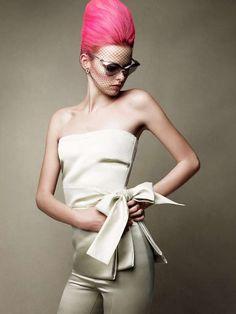Pour donner un look assez excentrique à cette jeune femme, le coiffeur a appliqué une coloration rose bonbon dans ses cheveux, mais a gardé les racines rousses. Il a ensuite relevé les cheveux sur le dessus de la tête, en leur donnant beaucoup de volume, avant de les ramener vers l'arrière. Le résultat est impressionnant.
