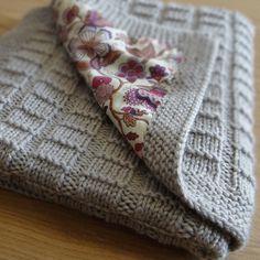 graue gestrickte Decke mit violett gemustertem Stoff