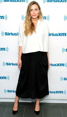 Elizabeth Olsen in a white top, black midi skirt and pumps