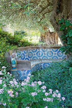 SICILY ITALY: SAN GIULIANO ESTATE: A MORROCAN INFLUENCED TILED SEATING AREA IN THE ARABIC GARDEN WITH OLIVE TREE, PELARGONIUM GRAVEOLENS, AND CONVOLVULUS MAURITANICUS SYN. C. SABATIUS