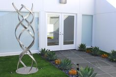 """Stainless steel sculpture """"Kismet"""" is beautifully set in a simple agave-filled entry garden."""