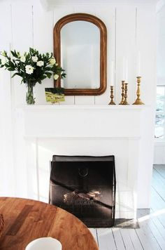 pretty white fireplace with candles and mirror