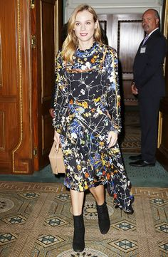 Diane Kruger wears a floral Preen dress with black boots and a Mark Cross top-handle bag