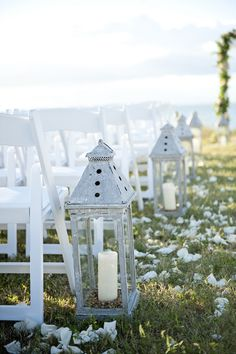beautiful lanterns line the aisle at this seaside wedding