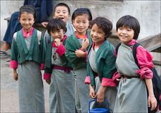 Bhutanese school girls in kira dress | national dress for women in Bhutan. It is an ankle-length dress consisting of a rectangular piece of woven fabric. It is wrapped and folded around the body and is pinned at both shoulders, usually with silver broaches, and bound at the waist with a long belt. The kira is usually worn with a wonju (long-sleeved blouse) inside and a short jacket or toego  outside.