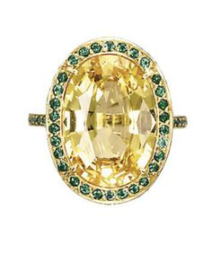 A COLOURED SAPPHIRE AND EMERALD RING   Set with a yellow sapphire weighing 10.16 carats to the circular-cut emerald surround, gallery and hoop, mounted in 18k gold