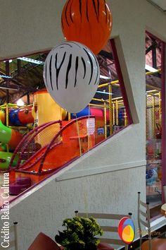 Decoração de mesa com balão mancha de animais de 11 polegadas inflado com gás hélio, fixados em arranjo de flores. Créditos: Decoração de balões: Balão Cultura (www.balaocultura.com.br) Local: Buffet Catavento