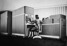 A woman works at an IBM 650 computer in 1955, which was designed for electro-mechanical punch card-processing.