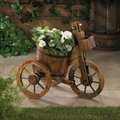 """Apple Barrel Planters Trio - This may be the most charming plant holder ever! The rain barrel potted plant holder features authentic black metal banding and is set on a wooden tricycle frame. From the wagon wheels to the little box on the front of the handlebars, this plant accessory is overloaded with country charm! Made from fir wood. Plants not included. Some assembly required. Dimensions:18"""" tall x 21"""" long x 12"""" wide"""