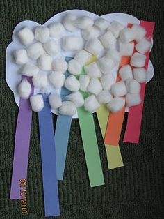 Rainbow made out of construction paper strips taped to half a paper plate covered with cotton balls.