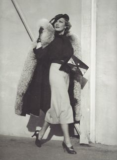 Marlène Dietrich, New York, 1930 phụ nữ mặc với váy dài quá đầu gối cùng với áo choàng lông dài thanh lịch quyến rũ với phần ví cầm ay sang trọng , gănng tay điểm nhấn