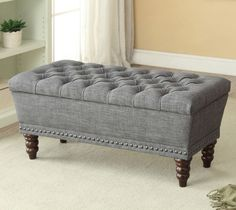 a beige or grey tufted storage bench with nailhead details and walnut legs. perfect for the end of a bed to hold extra blankets or whatever you like! 42w x 18h x 17d item number: 401-317-bg reg $469 sale $279 includes free delivery in edmonton
