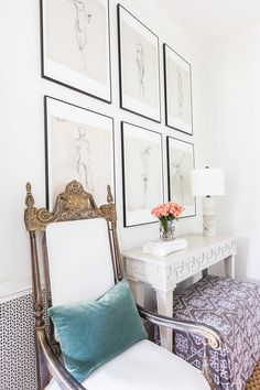 French Foyer. French Foyer Ideas. French style foyer features an art gallery placed over a white Greek key console table flanked by French chairs lined with blue velvet pillows. #FrenchFoyer Alyssa Rosenheck Photography. Castle Homes.