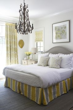 Yellow and gray bedroom features art over gray arched headboard on queen bed dressed in white bedding and zigzag pillows as well as yellow and gray striped bedskirt next to a distressed nightstand topped with Regina Andrew Keepsake Lamp atop gray jute rug situated under windows dressed in white and yellow lattice roman shades illuminated by beaded chandelier.
