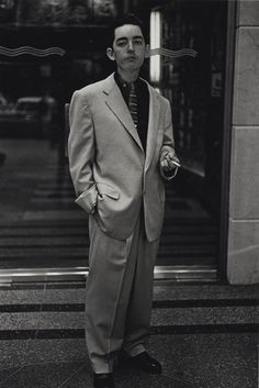 Diane Arbus  1923-1971  YOUNG MAN IN A BAGGY SUIT, N. Y. C.  signed and annotated with the Arbus Estate authentication number by Doon Arbus, the photographer's daughter, in ink and with the Arbus Estate copyright and reproduction rights stamps on the reverse, 1961 (Revelations, p. 56)  9 1/2  by 6 3/8  in. (24.1 by 16.1 cm.)