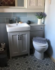 The grey bathroom furniture in this small bathroom creates a understated, sophisticated room.