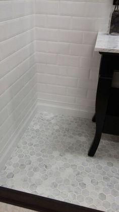 Carrera marble hexagon tile floor and subway tile walls