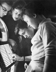 Teenagers choosing a song on the juke box, 1950′s