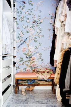 Dreamy walk-in closet with feminine wallpaper, marble floors, and a vintage bench