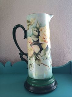 Very Pretty Hand Painted Limoges Pitcher. Yellow and pink roses on blue green background. Artist signed Ida Zoller. No markings in bottom. 12.5x6 at bottom.