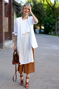A luxe day look is created with a fluid white tunic layered over camel culottes and worn with brown accessories.