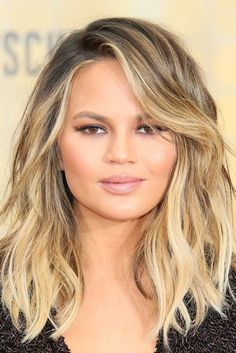 Looking for the best hairstyle trends for the summer? Try Chrissy Teigen's blonde lob with textured beach waves and side-swept bangs.