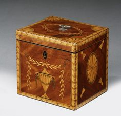 """A late George III single mahogany tea caddy decorated with marquetry garlands, urn, shell fan paterae & swags, banded with chevron & barber pole strining, with brass top handle. 4.5""""H, 4.5""""W, 4""""D from Richard Gardner Antiques"""