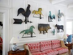 Collation of vintage weathervanes take the stage above the sofa in the living room.