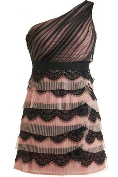 Rose Wafer Dress: Features a beautiful one-shoulder design with gathered black tulle overlay at the bodice, nipped and neat waistband, rose-colored foundation for pop, and a chic combination of pleated pink tiers and scalloped noir lace cascading down the skirt to finish.