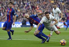 Real Madrid's midfielder Lucas Vazquez vies with Barcelona's Argentinian defender Javier Mascherano during the Spanish league football match FC Barcelona vs Real Madrid CF at the Camp Nou stadium in Barcelona on December 3, 2016.