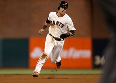 San Francisco Giants' Joe Panik (12) heads to third base from first on a  base hit by San Francisco Giants' Buster Posey (28) against the San Diego Padres in the first inning at AT&T Park in San Francisco, Calif., on Thursday, Sept. 25, 2014.  (Nhat V. Meyer/Bay Area News Group)