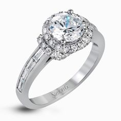The memorable halo of this white gold engagement ring is accentuated by .33 ctw round cut white diamonds and .47 ctw baguette cut diamonds.
