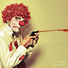 Disturbed Manic Clown In A Bloodstained Costume With A Depraved Look Shooting Blood From A Small Waterpistol Or Popgun In A Halloween Horror Concept by Ryan Jorgensen