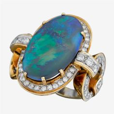 A black opal, diamond and fourteen karat gold ring  centering oval cabochon black opal weighing approximately: 14.00 carats; accented by round brilliant-cut diamonds; total diamond weight approximately: 1.50 carats.